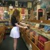 dükkanda plaklara bakan minili kız